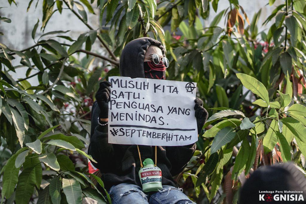Salah seorang massa aksi duduk sembari membentangkan poster agitasi.
